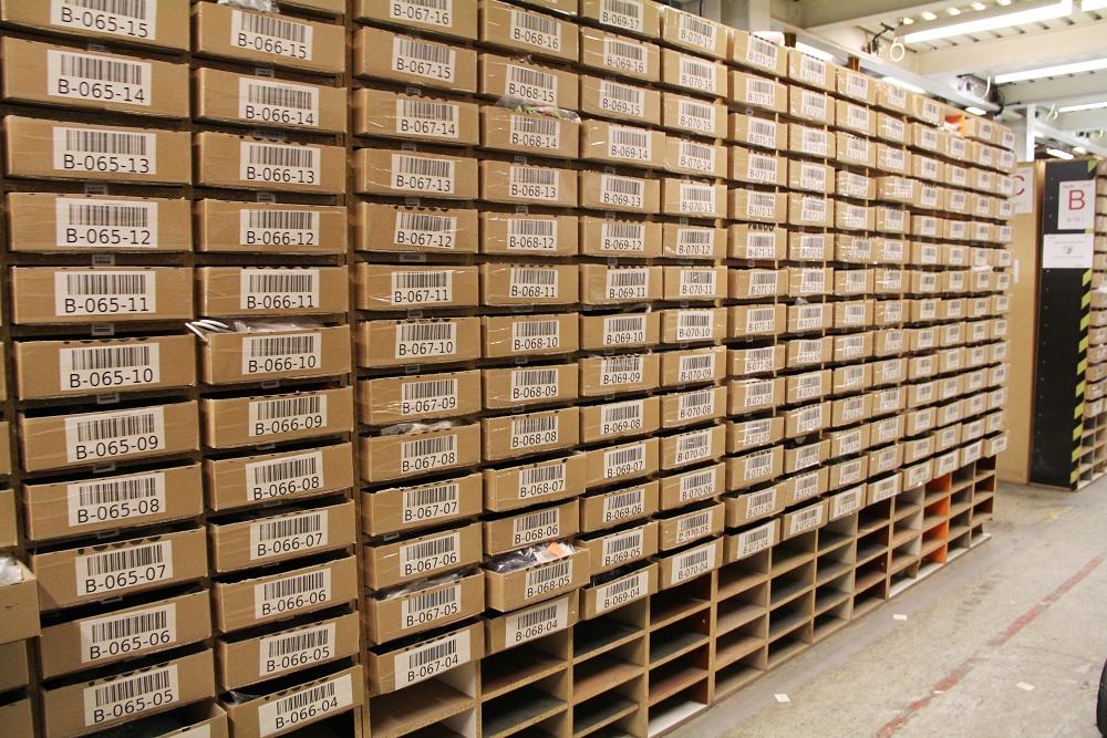 Feedo sklad: Hlavní sklad, ve kterém je uloženo již naskladněné zboží. V takových krabicích je uskladněno oblečení. Na každé krabici vidíte zřetelný čárový kód, který slouží k načtení zboží na čtečku.