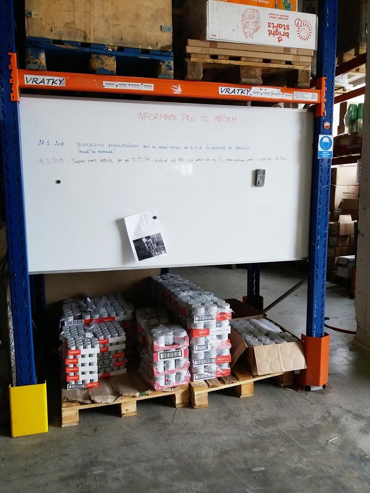 Feedo sklad: Sekce příjmu zboží. Na velké tabuli jsou napsané pokyny pro příjem zboží.